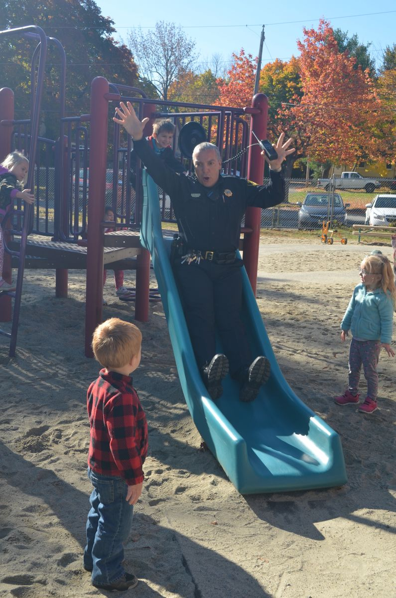 Gardiner Chief of Police Jim Toman enjoying turns on the slide at recess with a young boy at the Gardiner Early Learning Center.