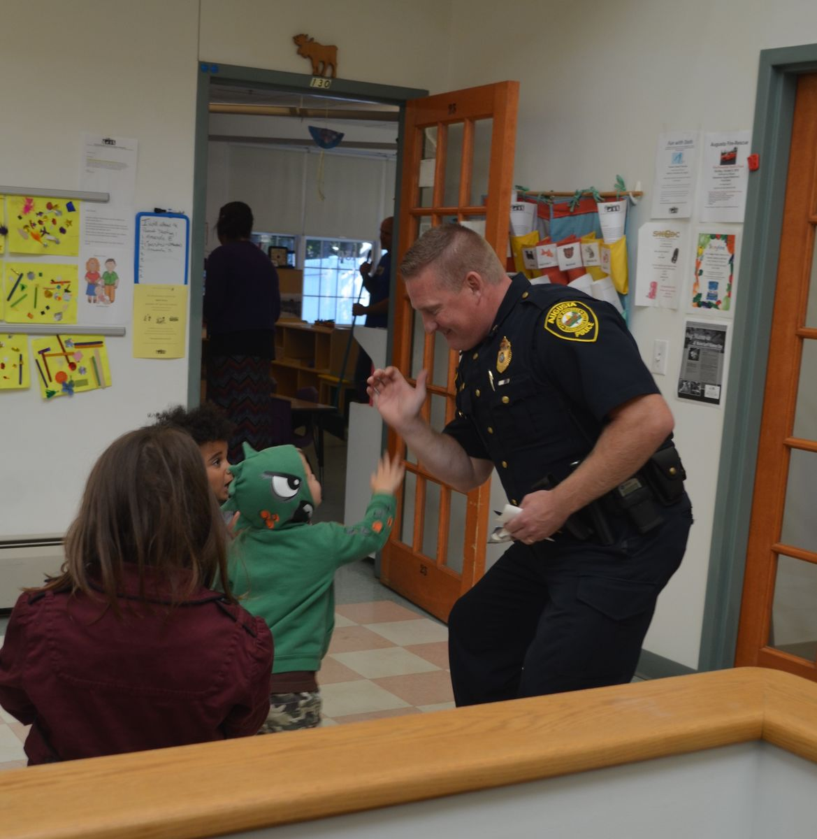 Augusta Police Chief Jared Mills high-fives a child at the local Magic Years Center, which offers Head Start programming.