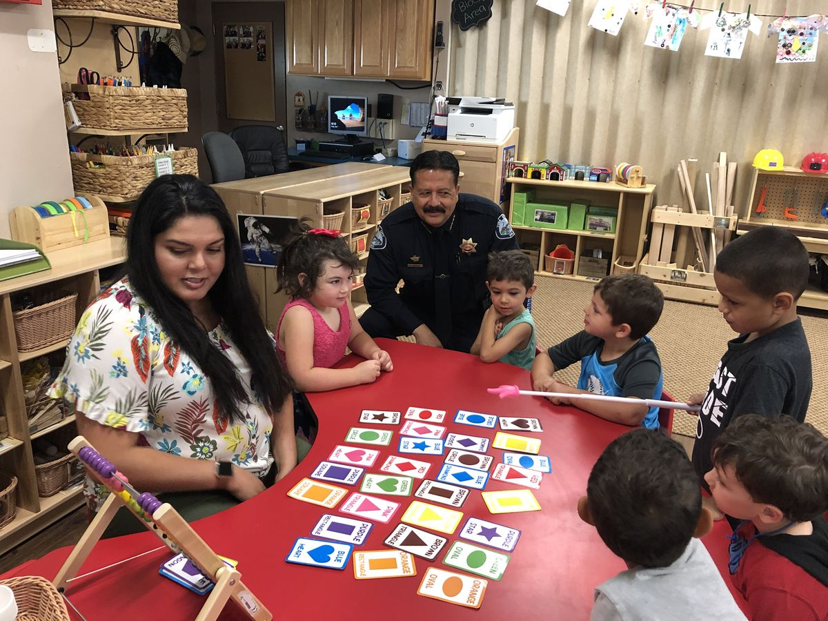 Yuba City Police Chief Robert Landon Interacts with students at Bernard Children's Center and helps them learn shapes and colors.