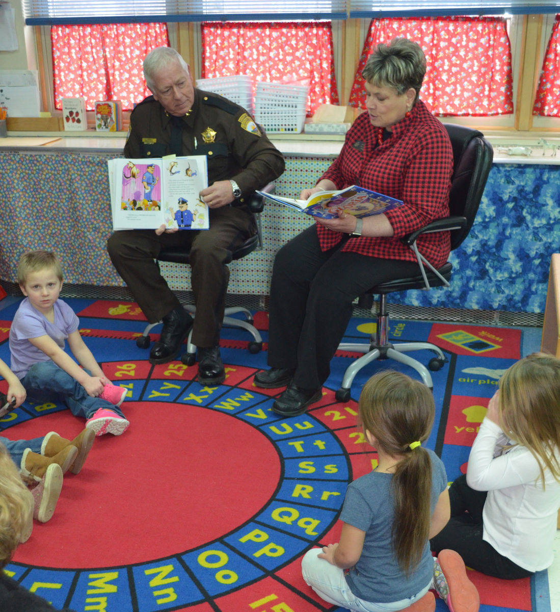 Washington County Sheriff Barry Curtis and State Senator Joyce Maker read a book to preschoolers at the Calais Elementary School.