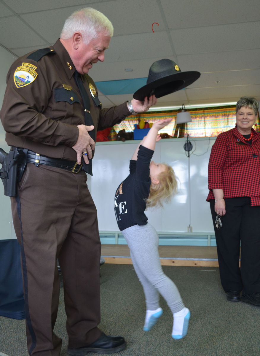 During a recent visit, Sheriff Barry Curtis and a young girl at the Washington County Community College's Head Start child care program play a game with his hat.