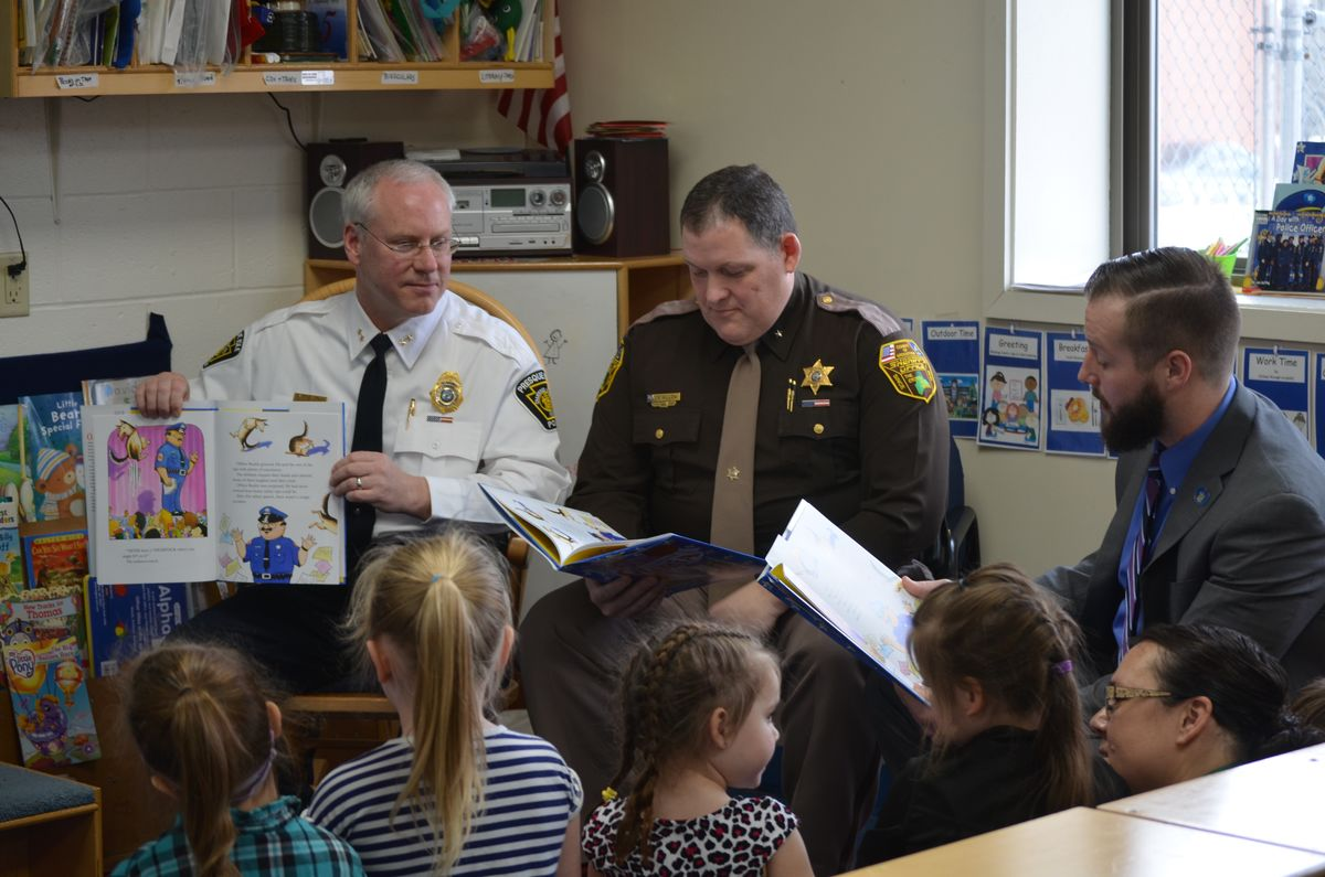 "Presque Isle Chief Matt Irwin, Aroostook County Sheriff's Office Chief Deputy Shawn Gillen and State Representative Harold ""Trey"" Stewart III read a book to students at the Aroostook Community Action Program's Head Start classroom operated within the Presque Isle Regional Career and Technical Center's Early Childhood Education program."