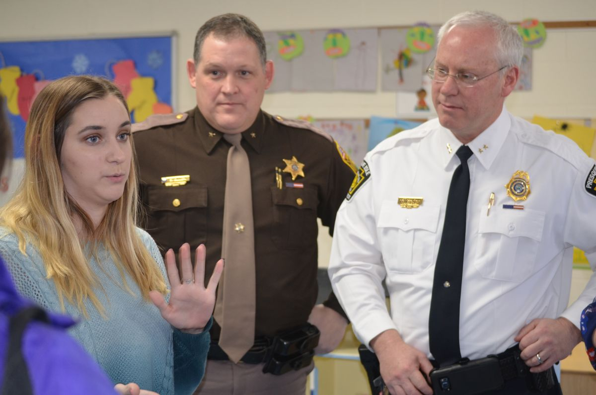 Aroostook County Sheriff's Office Chief Deputy Shawn Gillen and Presque Isle Chief Matt Irwin listen to a high school student enrolled in the Presque Isle Career and Technical Center's early childhood education program where she gets to practice her learning by working with preschool students in the Head Start classroom there.