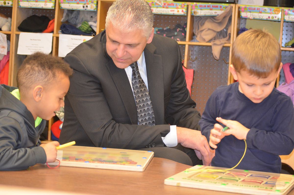 Auburn Chief of Police Phil Crowell volunteering to work with Head Start students at the Promise Early Education Center. Chief Crowell is a member of the Center's Board of Directors.